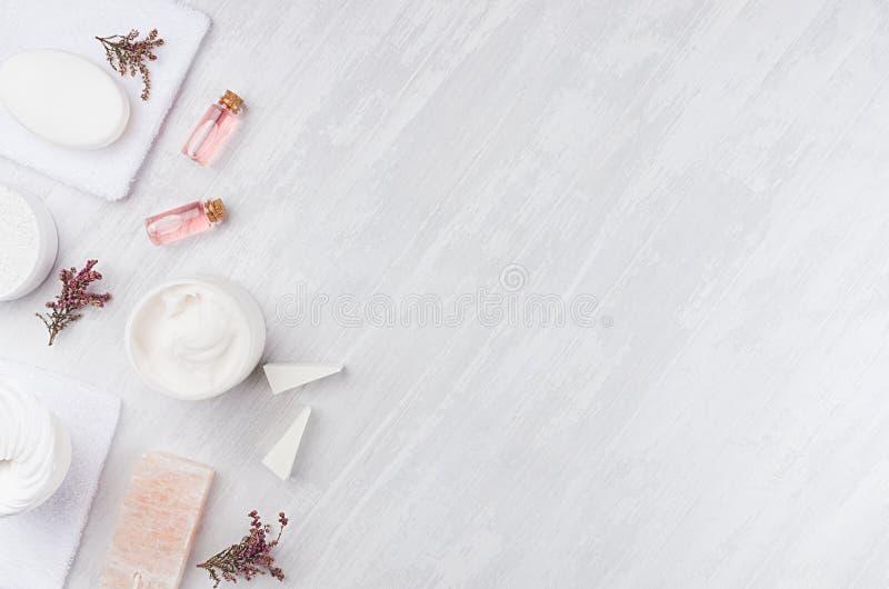 工艺品自然化妆用品-白色奶油、肥皂、黏土、玫瑰油、毛巾、桃红色花和浴辅助部件在柔光白色 库存照片