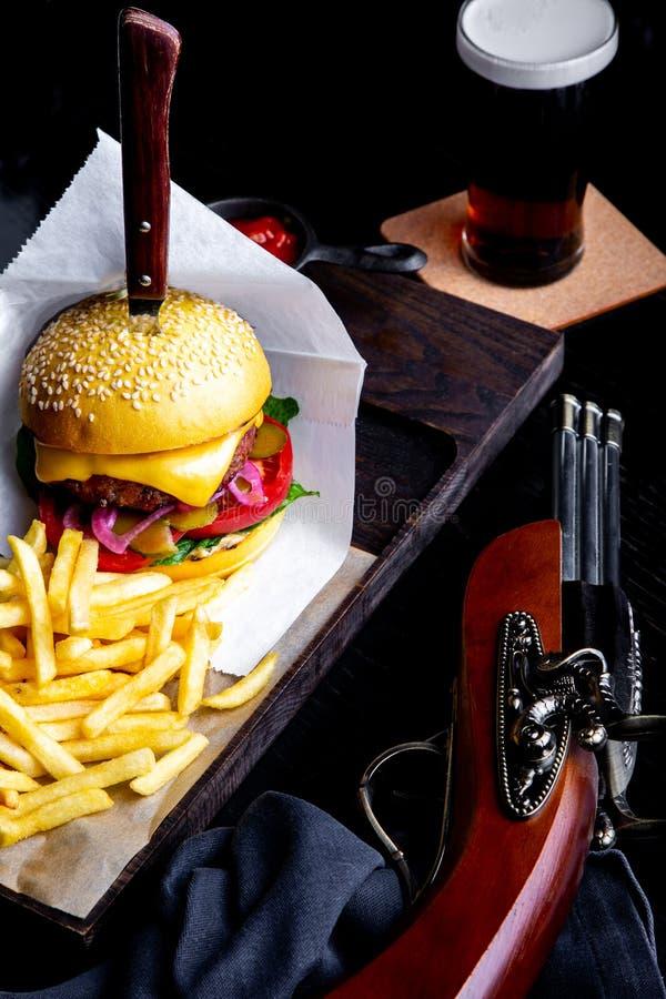 工艺牛肉汉堡和薯条在桌上在餐馆有杯的啤酒在黑暗的背景 现代快餐午餐 免版税库存照片