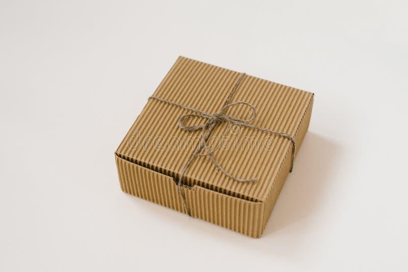 工艺礼物盒栓与麻线有在米黄背景 缎带包装为生日 免版税图库摄影