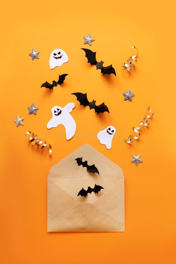工艺纸信封和黑纸棒飞行在橙色背景,顶视图 免版税库存图片