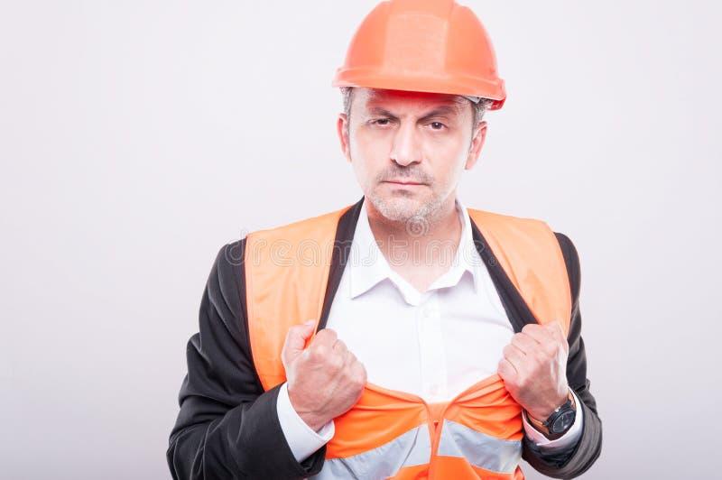 工头佩带的安全帽和背心英雄射击  库存照片