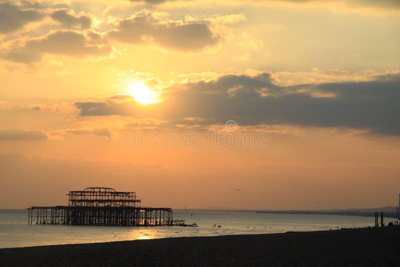 左站立在海的老布赖顿码头遗骸在日落,英国,英国 图库摄影
