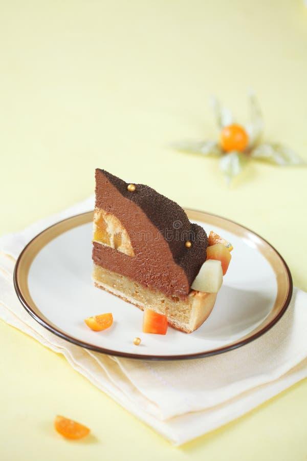 巧克力、芒果和马卡达姆坚果蛋糕片断  免版税库存照片