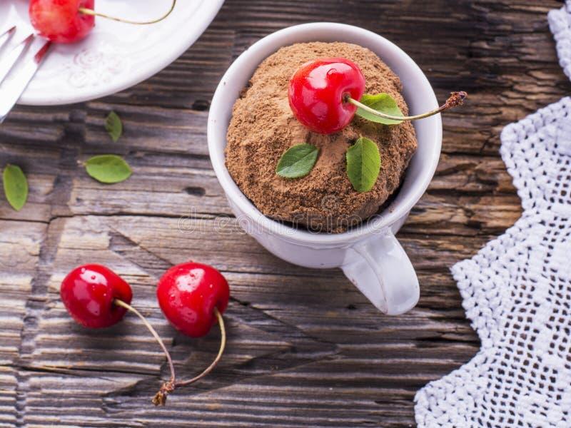 巧克力与奶油和樱桃的杯子蛋糕在木背景 库存图片