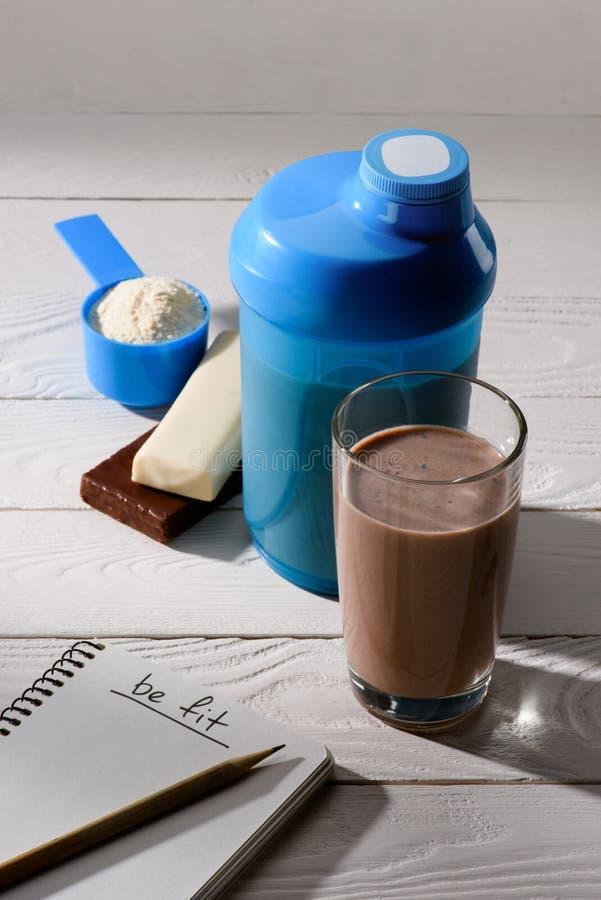 巧克力与强身糕和笔记本的蛋白质震动与是在白色的适合的标志 库存图片