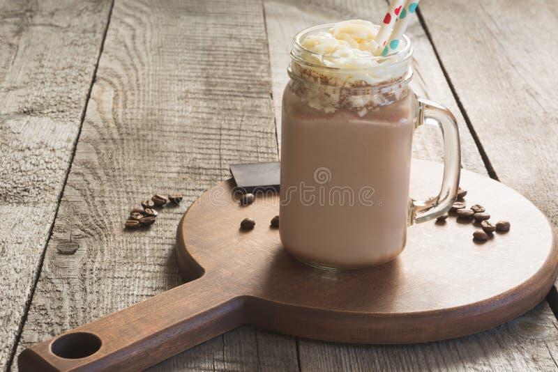 巧克力与打好的奶油的咖啡奶昔在葡萄酒木背景的玻璃金属螺盖玻璃瓶服务 甜饮料 图库摄影