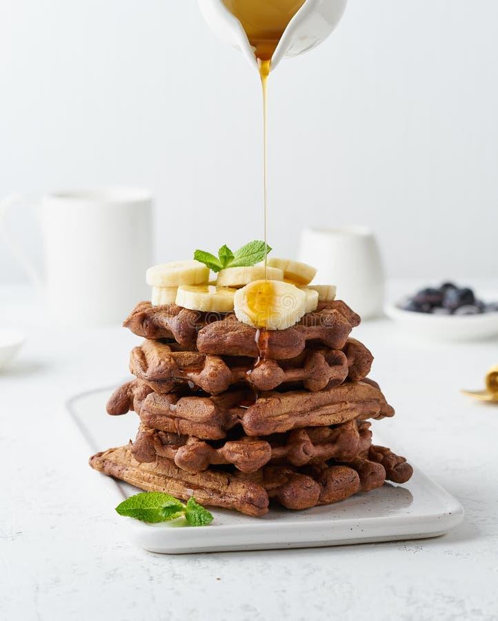 巧克力与枫蜜流程的香蕉奶蛋烘饼在牛奶罐,在白色桌,侧视图,垂直上的盛奶油小壶 甜早午餐 免版税库存图片