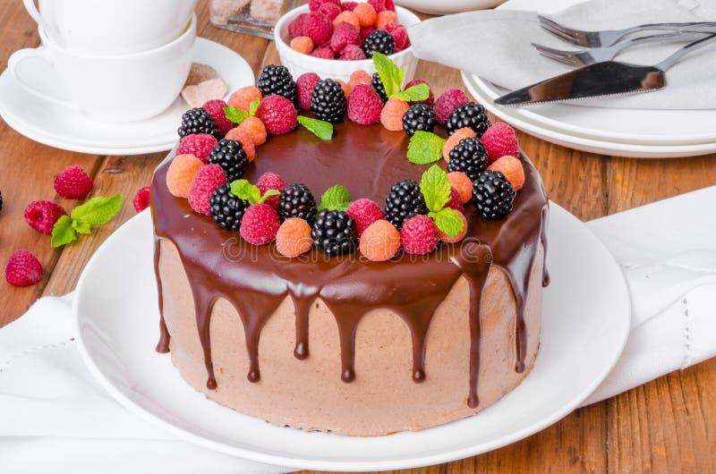 巧克力与樱桃装填的夹心蛋糕和在上面的新鲜的莓果 库存图片