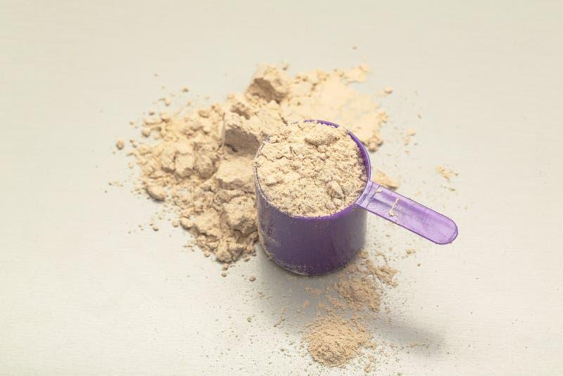 巧克力与瓢的乳清蛋白粉末在灰色背景 免版税库存照片