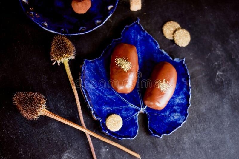 巧克力与金粉末的土豆蛋糕在深蓝色板材 厨房艺术工作  库存照片