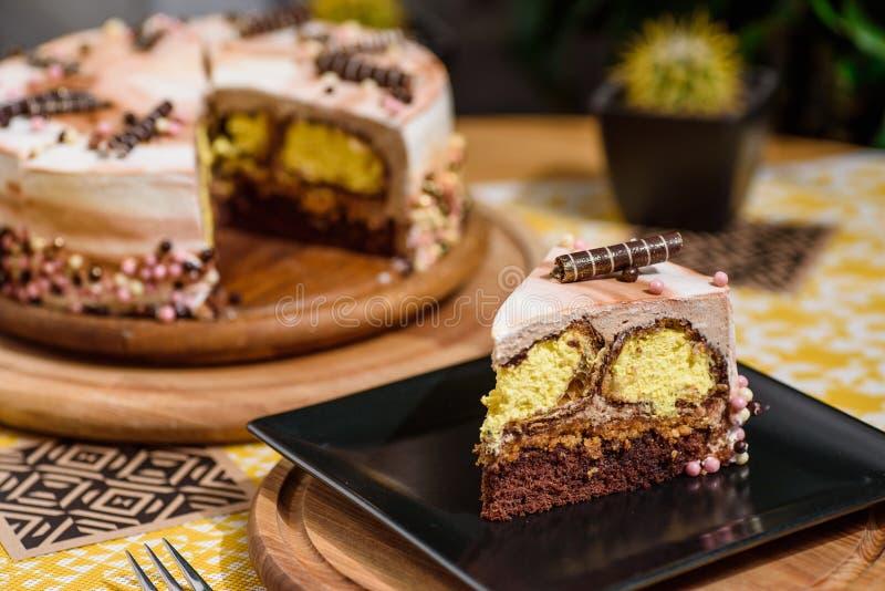 巧克力与黄色装填和美丽的咖啡釉的夹心蛋糕,装饰用小管和酥皮点心小珠 库存照片