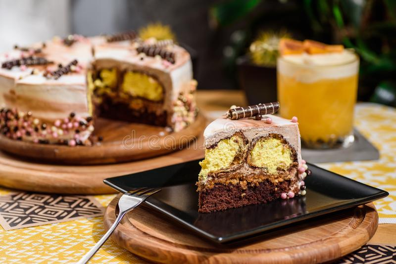 巧克力与黄色装填和美丽的咖啡釉的夹心蛋糕,装饰用小管和酥皮点心小珠 库存图片