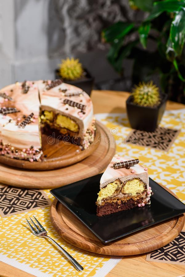 巧克力与黄色装填和美丽的咖啡釉的夹心蛋糕,装饰用小管和酥皮点心小珠 图库摄影