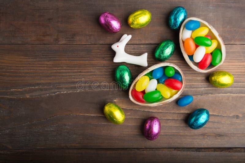 巧克力五颜六色的鸡蛋用在木背景的野兔 免版税库存照片