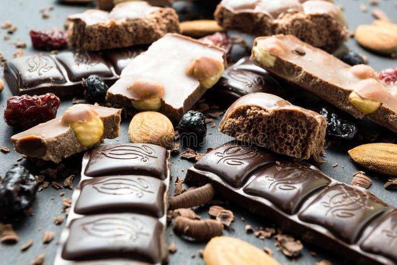 巧克力和干果子不同形式在黑背景 免版税图库摄影