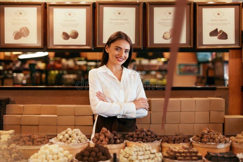 巧克力商店 女性卖主在糖果店商店 免版税库存图片