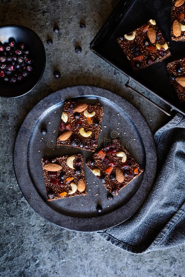 巧克力喘气了奎奴亚藜酒吧用被冰冻干燥的黑醋栗、糖煮的番木瓜、腰果、杏仁和蔓越桔 免版税库存图片