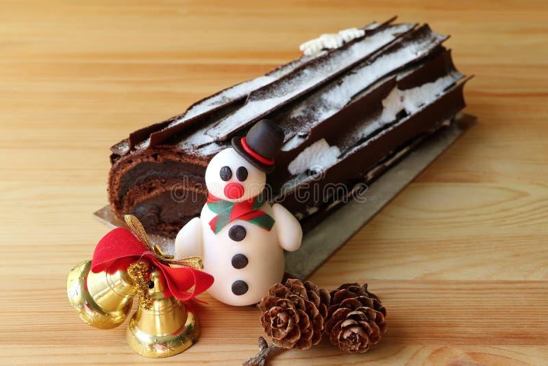 巧克力圣诞柴蛋糕或Buche de Noel Decorated用雪人小杏仁饼和干燥杉木锥体,在木表上的圣诞节装饰品 免版税库存照片