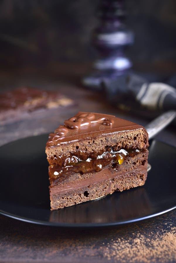 巧克力在一个黑色的盘子的Sacher奶油蛋糕片断  图库摄影