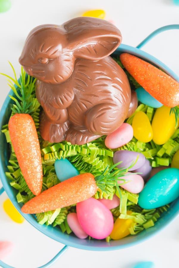 巧克力在复活节篮子的复活节兔子特写镜头用微型红萝卜和糖果鸡蛋在白色背景 库存照片