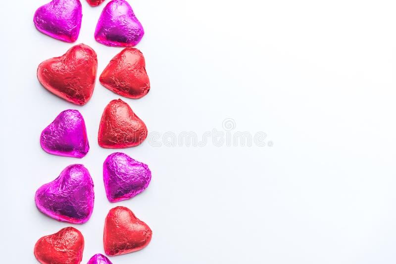 巧克力在红色和桃红色箔包裹的华伦泰心脏在白色背景的左面 图库摄影