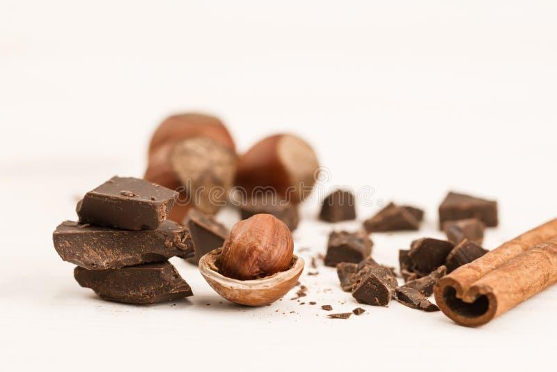 巧克力块、榛子和桂香在木背景,特写镜头 免版税库存图片