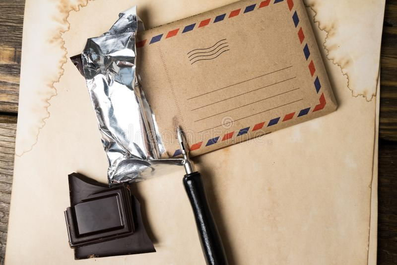 巧克力块和钢笔在葡萄酒纸,一张老木桌说谎 嘲笑 免版税库存照片