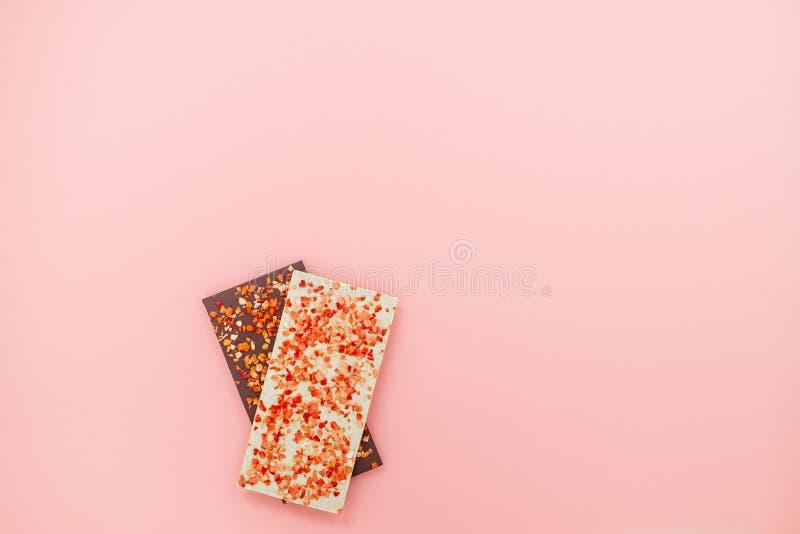 巧克力块用在桃红色抽象背景食物视图平的被放置的糖果手黑暗的点心甜豪华褐色的干草莓 免版税库存照片