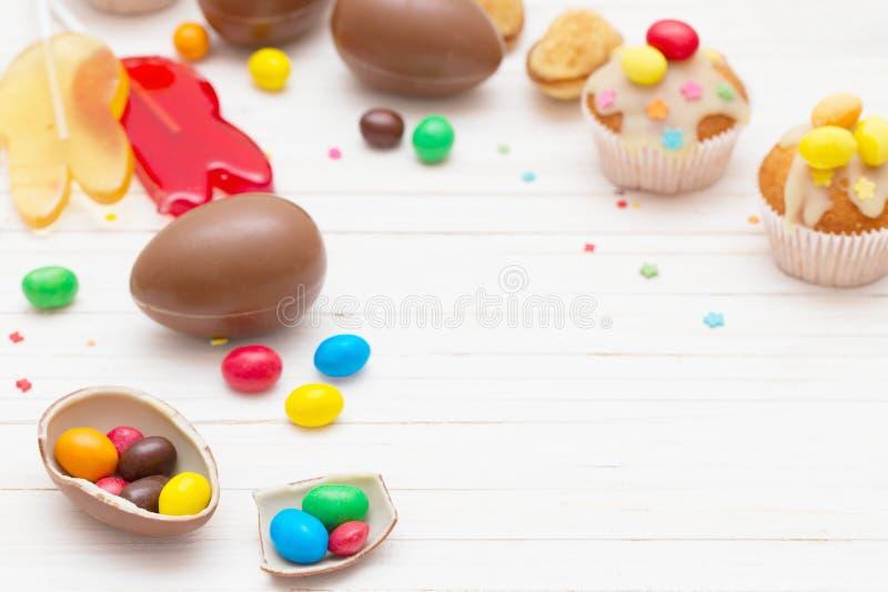巧克力复活节彩蛋和杯形蛋糕在木背景 免版税库存图片
