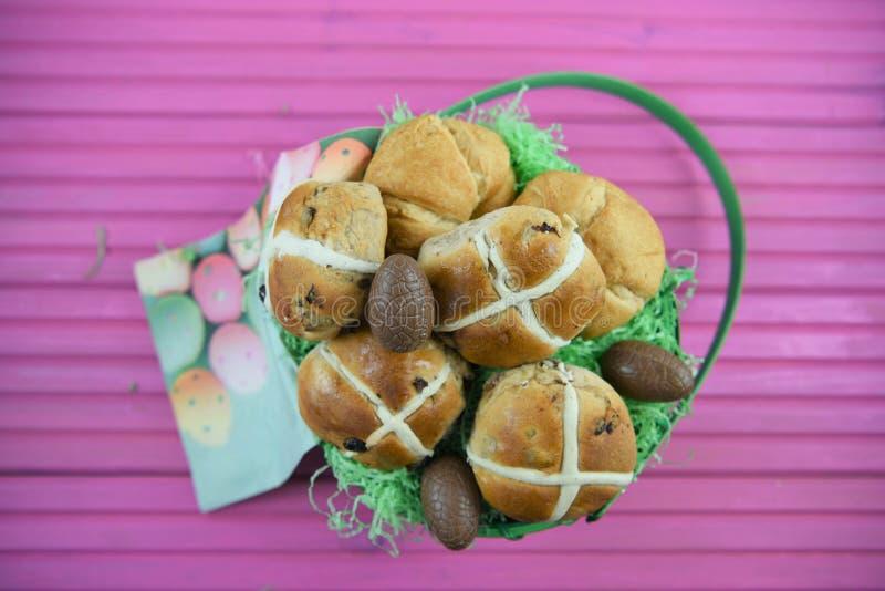 巧克力复活节彩蛋和食物在一个礼物篮子有桃红色桌背景 库存图片