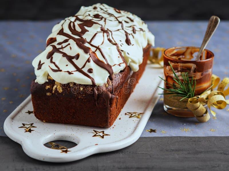 巧克力大面包蛋糕装饰用被鞭打的奶油色结霜的和熔化的巧克力 圣诞节和新年庆祝概念 库存图片