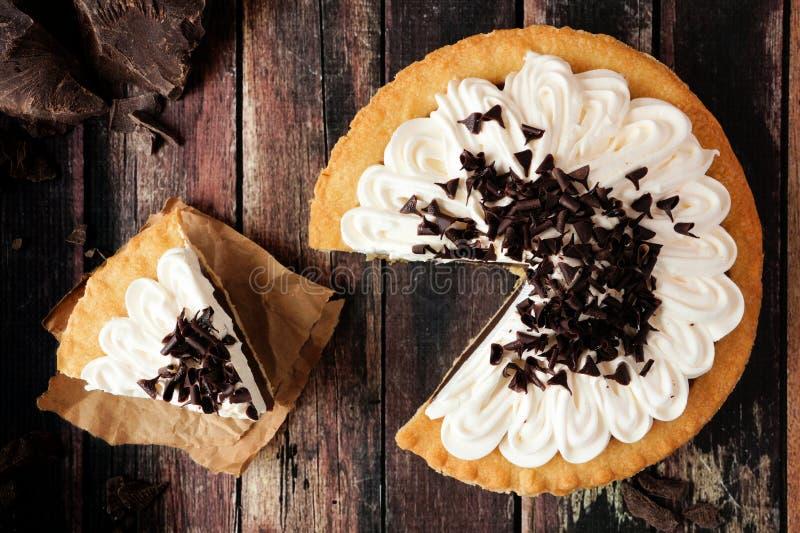 巧克力奶油馅饼,与在黑暗的木头去除的切片的顶视图场面 图库摄影