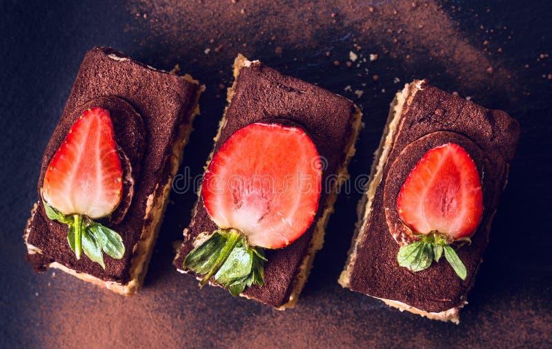 巧克力提拉米苏蛋糕用在黑板岩的草莓 免版税库存照片