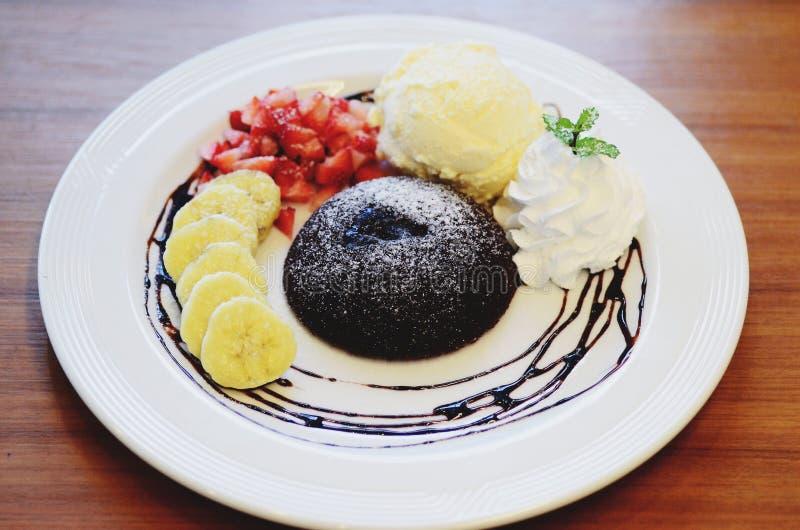 巧克力方旦糖用草莓和香草冰淇淋装饰的熔岩蛋糕 免版税库存图片