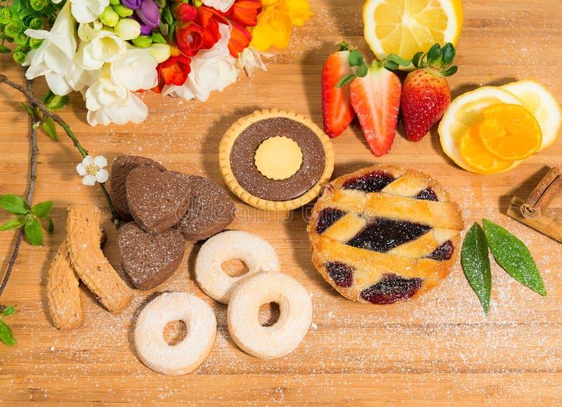 巧克力曲奇饼、脆饼和馅饼宽选择与果子果酱和可可粉奶油、草莓、桂香和春天花 免版税图库摄影
