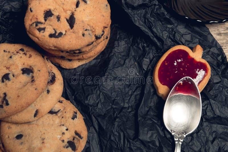 巧克力曲奇饼,在匙子附近的饼干用在黑桌背景的果酱 顶视图 库存照片