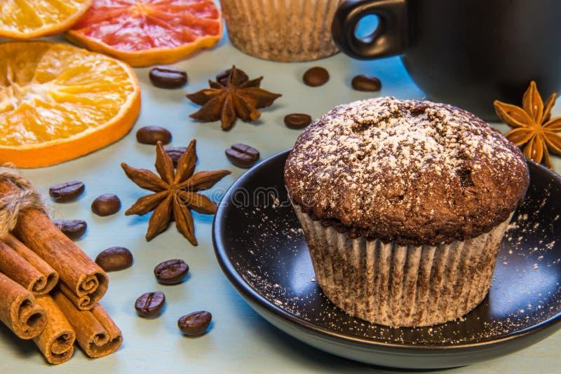 巧克力杯形蛋糕洒与在一个黑色的盘子的糖粉末在一杯咖啡旁边用桂香豆和切好的桔子 库存图片
