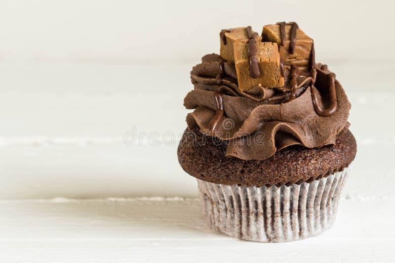 巧克力杯形蛋糕装饰用微型乳脂软糖在白色鲁斯摆正 库存图片