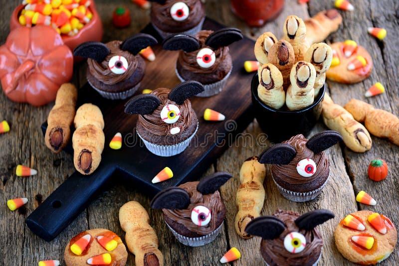 巧克力杯形蛋糕`击`和一种油脂含量较高的酥饼`巫婆` s手指` -万圣夜的庆祝的可口面包店甜点 免版税库存照片