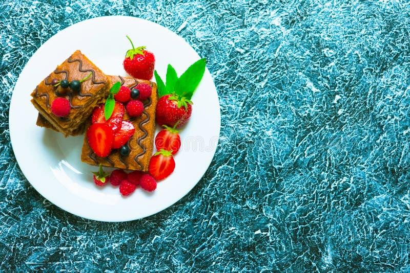 巧克力松糕用奶油色和新鲜的莓果 在织地不很细灰色背景的夏天点心 r 免版税库存照片