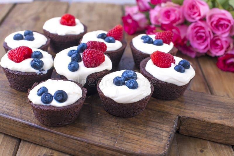巧克力松饼用莓和蓝莓和白色乳酪奶油,在一个棕色木板 新鲜的桃红色玫瑰花束  库存照片