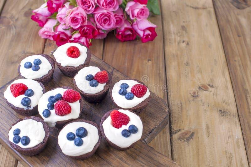 巧克力松饼用莓和蓝莓和白色乳酪奶油,在一个棕色木板 新鲜的桃红色玫瑰花束  库存图片