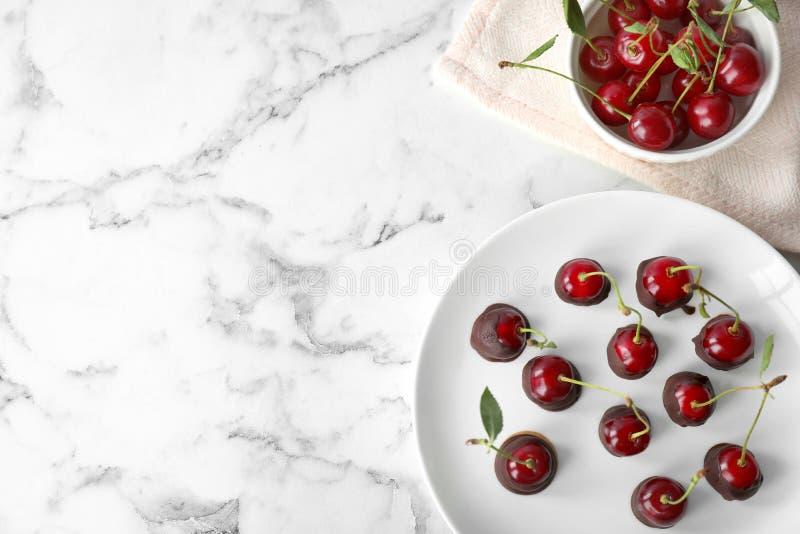 巧克力板材蘸了在白色大理石桌,平的位置上的樱桃 库存图片