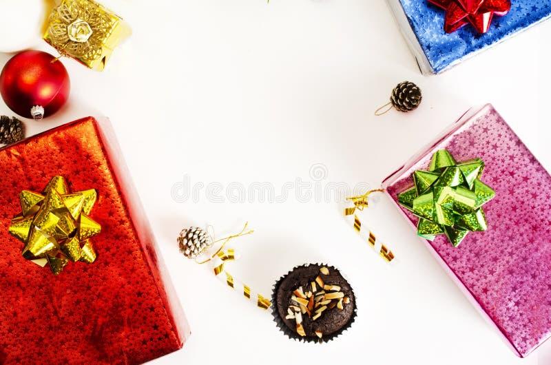 巧克力果仁巧克力和五颜六色的giftbox装饰在白色背景为圣诞节假日 免版税库存图片