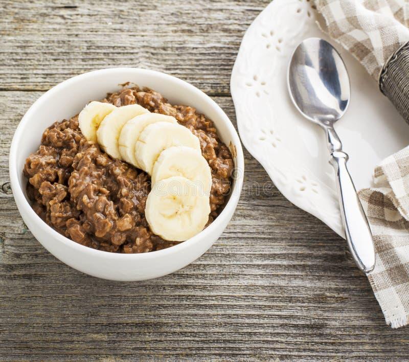 巧克力燕麦粥与切片的早餐一个成熟苦涩好巧克力香蕉和片断在一个白色陶瓷碗的 免版税库存照片