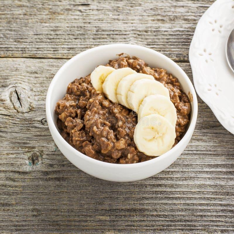 巧克力燕麦粥与切片的早餐一个成熟苦涩好巧克力香蕉和片断在一个白色陶瓷碗的 库存照片
