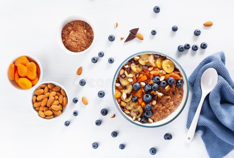 巧克力燕麦粥粥用蓝莓,坚果,香蕉,健康早餐顶视图的杏干 免版税图库摄影