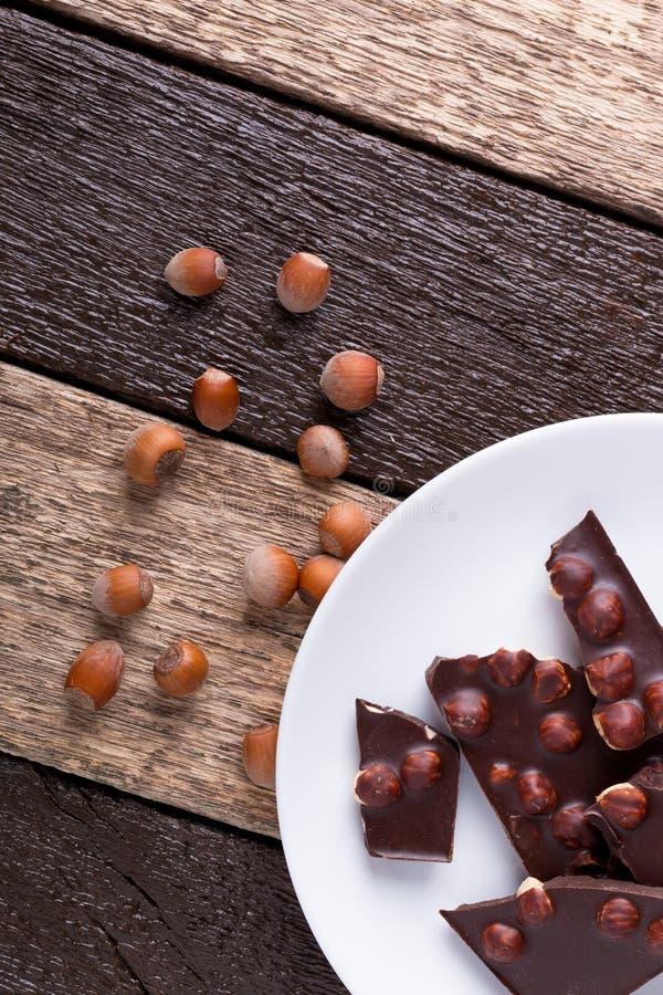 巧克力片与在白色板材木背景的榛子坚果 顶视图 复制空间 库存照片