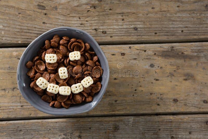 巧克力玉米片用形成在碗的蜂窝谷物兴高采烈的面孔 免版税库存图片