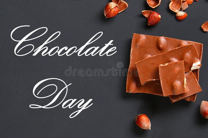巧克力用榛子、咖啡薄菏和五谷在一张深灰桌上的 顶视图 7月11日是天巧克力 免版税库存图片